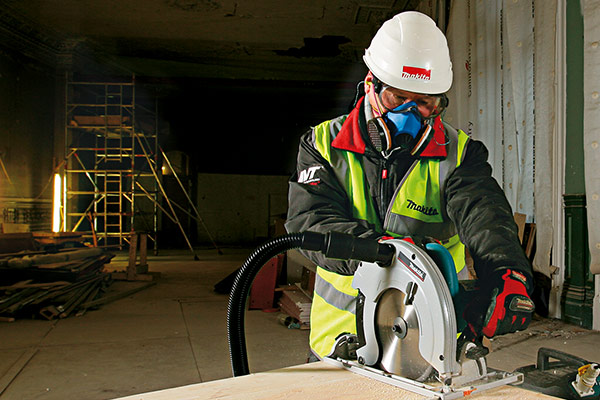 Makita - Professional in safety clothing using a saw with dust extraction - EPTA Member